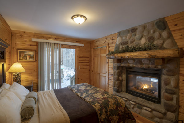 Oak Ridge Romantic Luxury Cabin bedroom with double sided glass fireplace