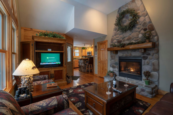 Living room with stone fireplace and flat screen tv