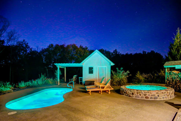 Private romantic lit pool and cold plunge with 2 lounge chairs, night stay in background
