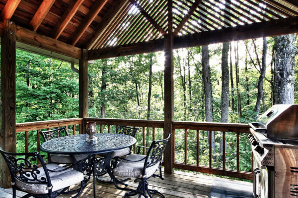 Wooden porch, gas grill and outdoor dining area, summer trees in background