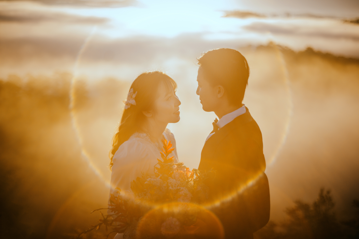 bride and groom gazing at each other while sun sets